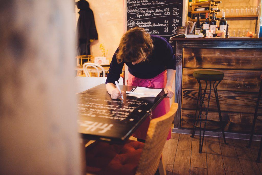 Die Restaurantleiterin beschriftet die Tafeln mit dem Tagesmenü.